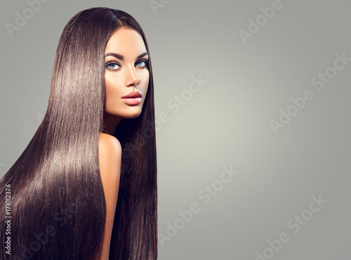 Beautiful long hair. Beauty woman with straight black hair on dark background © Subbotina Anna