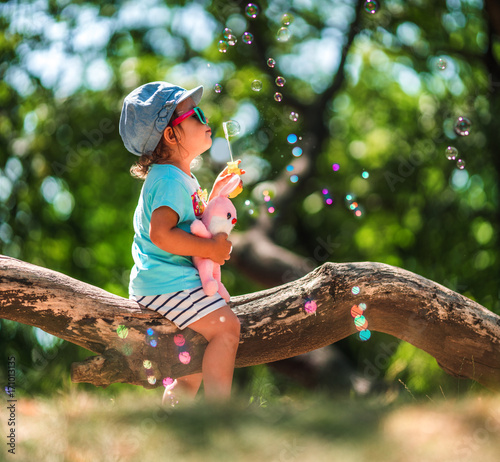 One years old little girl blowing soap bubbles in summer park