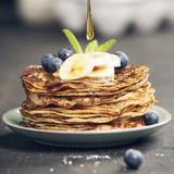 Homemade pancakes with fresh bananas, blueberries and honey