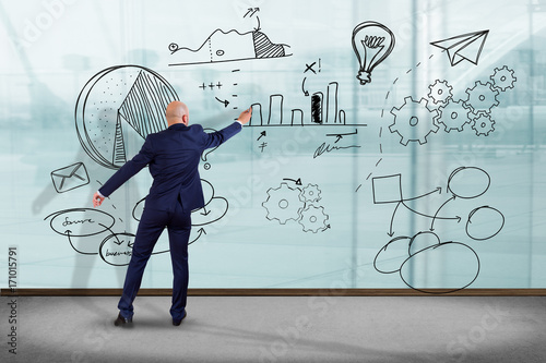 Wall mural Businessman in front of a wall writing on a business reminder interface application - Technology concept
