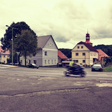Stvolinky, Czech republic - August 19, 2017: route 15 with moving motorcycle on road 15 leading around green square in summer holidays in Machuv kraj czech tourist area in polaroid stylization