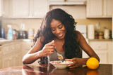 Fototapety Smiling young woman eating breakfast at table in kitchen