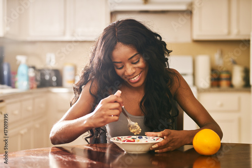 Smiling young woman eating breakfast at table in kitchen