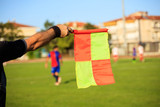 Soccer (football) referee assistant with flag on the field