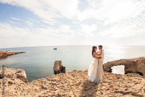 Fotobehang Cyprus Elegant smiling young bride and groom walking on the beach, kissing and having fun, wedding ceremony near the rocks and ocean.