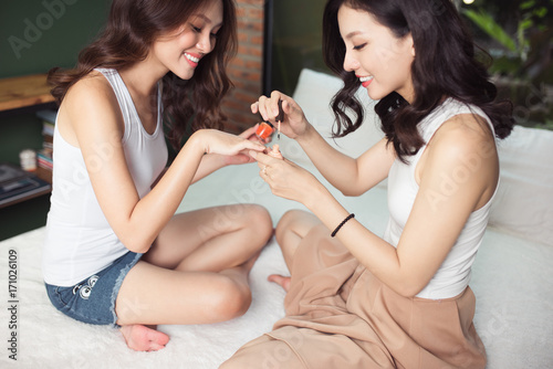 Fotobehang Manicure Two asian women in the bedroom on the bed paint their nails and have fun