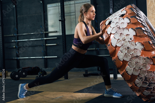 Wall mural Side view portrait of strong young woman flipping heavy tire during cross workout in modern gym