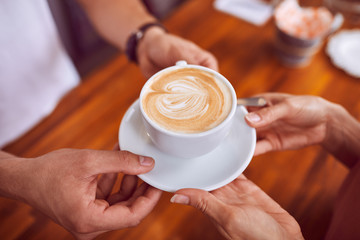Close-up of coffee with latte art being given to female customer by barista