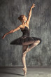 Young beautiful woman prima theater in a black festive pack, white pantyhose, white pointe shoes beautifully dancing russian ballet in a black dance studio