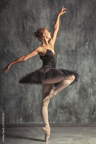 Young beautiful woman prima theater in a black festive pack, white pantyhose, white pointe shoes beautifully dancing russian ballet in a black dance studio © Виталий Сова