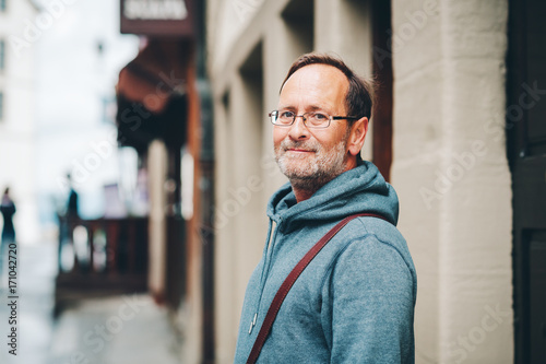 Poster Outdoor portrait of 50 year old man wearing blue hoody and eyeglasses