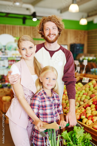 Family of vegetarians buying vegs and fruit in supermarket