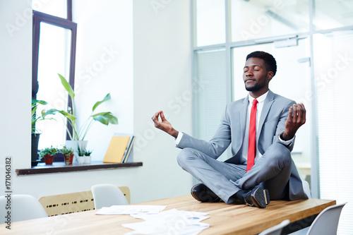 Elegant businessman in red tie and grey suit sitting in pose of lotus on desk