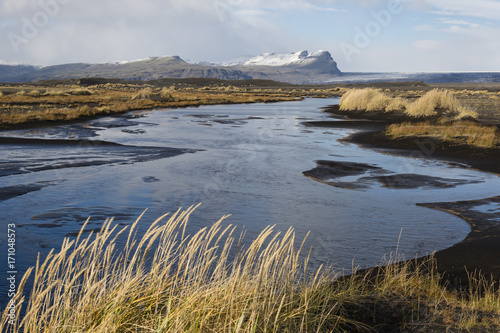 Fotobehang Grijs Autumn landscape in Iceland with a river, black sand and dry grass in foreground