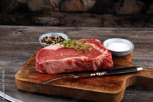 Poster Steakhouse Raw fresh meat Ribeye Steak, seasoning and meat fork on dark background