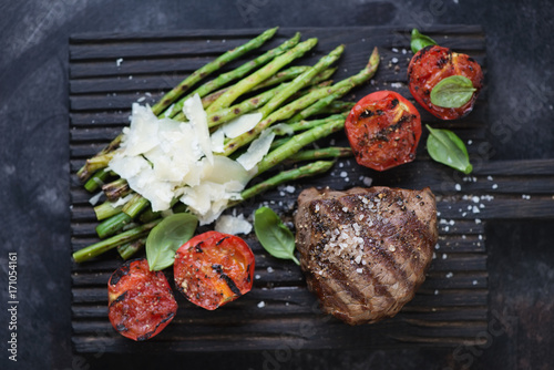 Foto op Plexiglas Steakhouse Close-up of grilled beef medallion steak with asparagus and tomatoes on a black wooden serving board, flat-lay