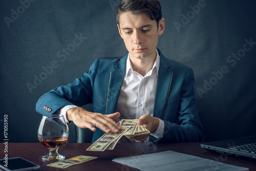 Businessman in suit throwing money in the form of hundred dollar bills. Concept of Investments and successful business