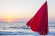 Quadro Dettaglio di un ombrellone rosso con il tramonto sul mare come sfondo. Il sole vicino ormai all'orizzone dona le tonalità calde a questa giornata di vacanza. Il mare è calmo e con poche onde.