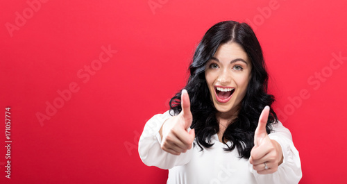 Happy young woman giving thumbs up on a solid background - 171057774