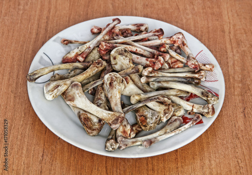 Heap of picked chicken bones on a plate. Poster