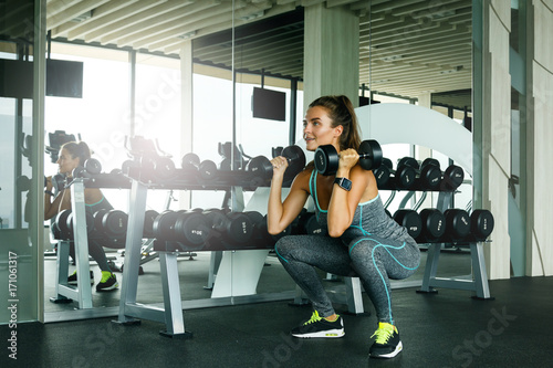 Woman working out with dumbbells in gym © blackday