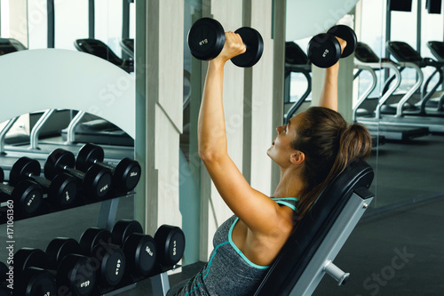 Wall mural Woman working out with dumbbells in gym