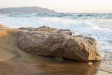 Dettaglio di uno scoglio di pietra che sta sulla spiaggia e viene bagnato dalle onde. L'acqua del mare ogni tanto arriva a riva e bagna la battigia della costa. - 171070338
