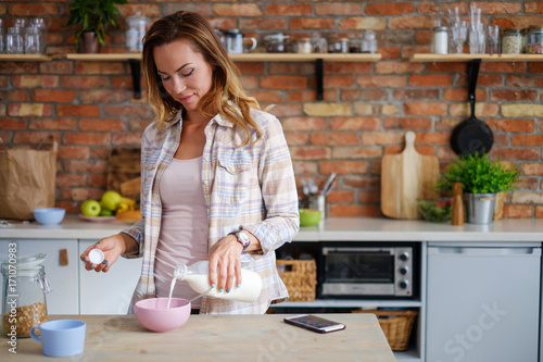 Woman making cereals for a breakfast - 171070983