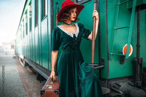 Woman in red hat against old railway wagon