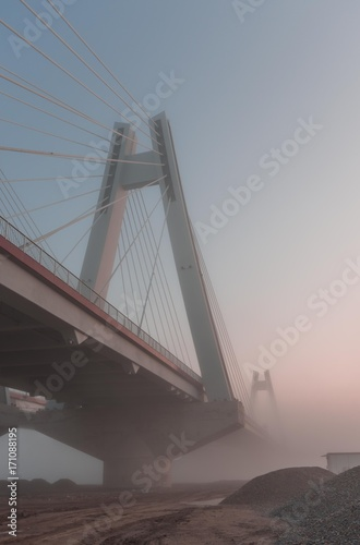Fotobehang Bruggen Cable stayed bridge, Krakow, Poland, in the morning fog over Vistula river