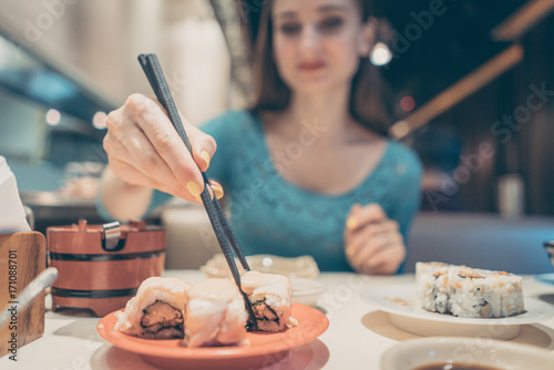 Foto op Aluminium Sushi bar Woman eating sushi food in Japanese restaurant with sticks