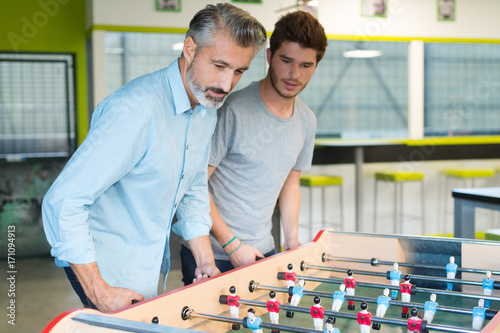 businesspeople playing table soccer game during their free time Poster