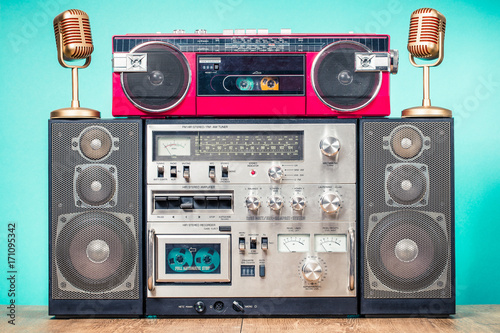 Poster Retro outdated HI FI stereo cassette boom box system, red radio tape recorder from 80s and golden microphones on table front aquamarine background