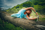 young woman practice yoga outdoor on huge fell tree on the mountain - 171100981