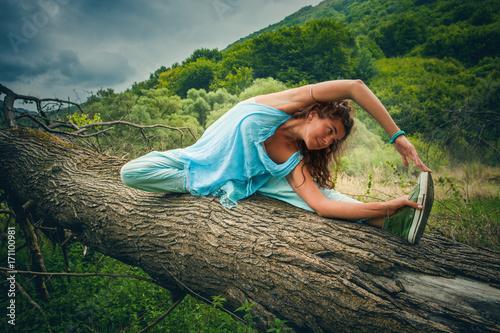 Plakat young woman practice yoga outdoor on huge fell tree on the mountain