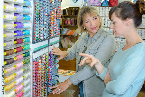 seamstress choosing threads at a shop Poster