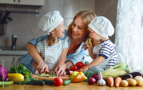 Healthy eating. Happy family mother and children  prepares   vegetable salad in kitchen. - 171131723