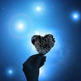 Hand with a heart shape and starry background.  - 171138149