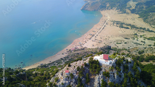 Foto op Plexiglas Beige August 2017: Aerial drone photo of famous Tsabika monastery overlooking iconic Tsabika bay from the cliff with clear turquoise waters, Rhodes island, Aegean, Dodecanese, Greece