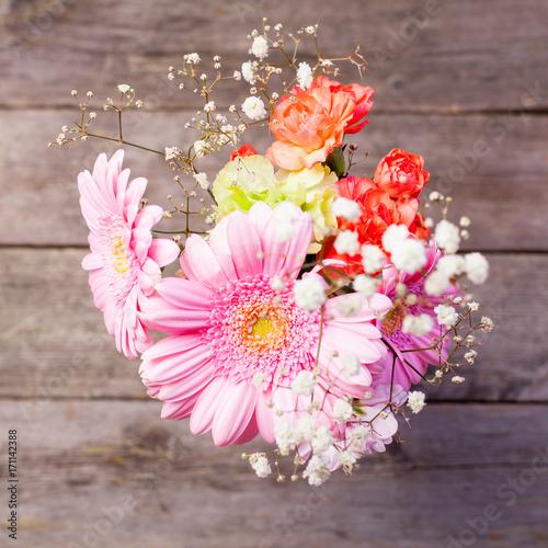 Fotobehang Gerbera en bukett blommor på trä bakgrund