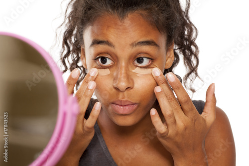 a young dark skinned woman applies a concealer under the eyes with her fingers