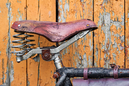 Fotobehang Fiets Old bicycle seat on the background of painted wooden planks