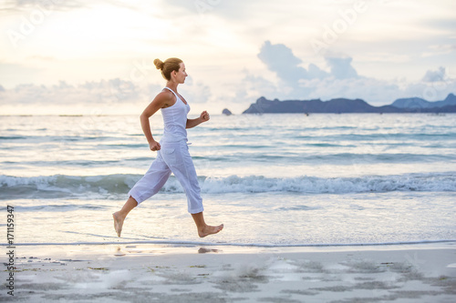Caucasian woman jogging at seashore - 171159347