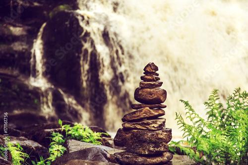Stone pyramid near a tropical waterfall.