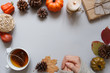 Autumn background. Female hands, cup of tea, autumn decoration on gray background.