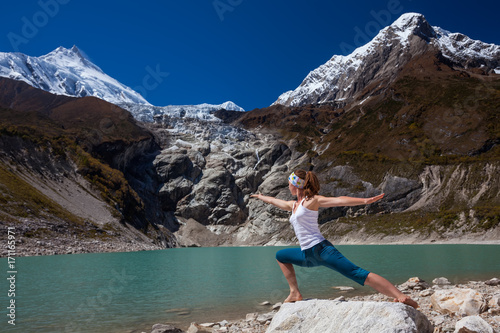 Fotobehang School de yoga Woman is doing yoga excercises near big lake on the Manaslu circuit trak in Nepala