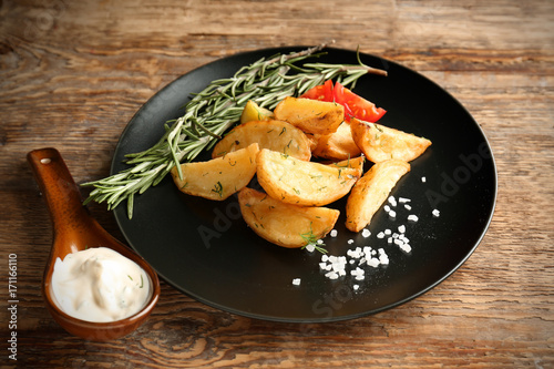 Fotobehang Kruiden 2 Plate with delicious baked potato wedges and sauce on table
