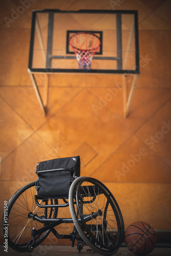 Basketball and Wheel chair in a lonely atmosphere, in concept Disappointment, injury, discouragement, despair - 171175549