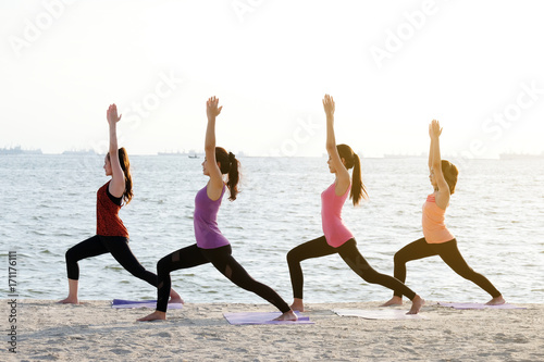 Fotobehang School de yoga Group of young healthy women practicing yoga on the beach, healthy lifestyles, wellness, well being