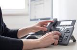 Telefon auf Schreibtisch, Griff zum Hörer